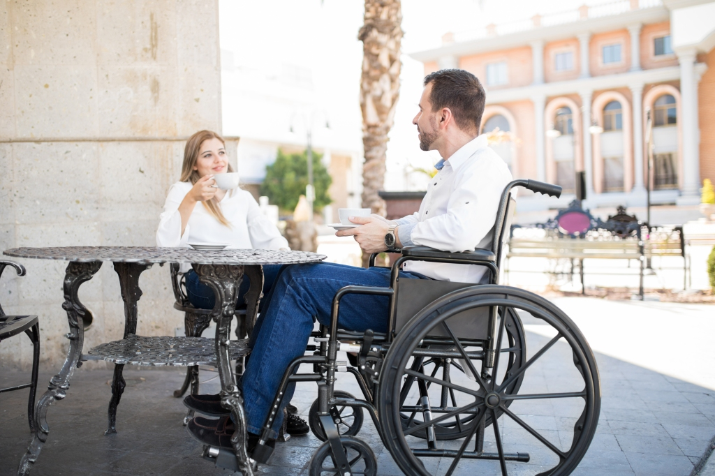 A young man and a young woman enjoying coffee. The young man is a wheelchair user and he's seated at an accessible table outside of a cafe.