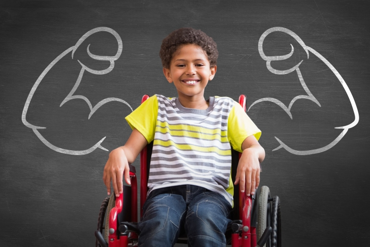 A young boy in a wheelchair smiling at the camera.  A chalkboard is positioned behind him with chalk arms with big muscles are drawn on each side of him.