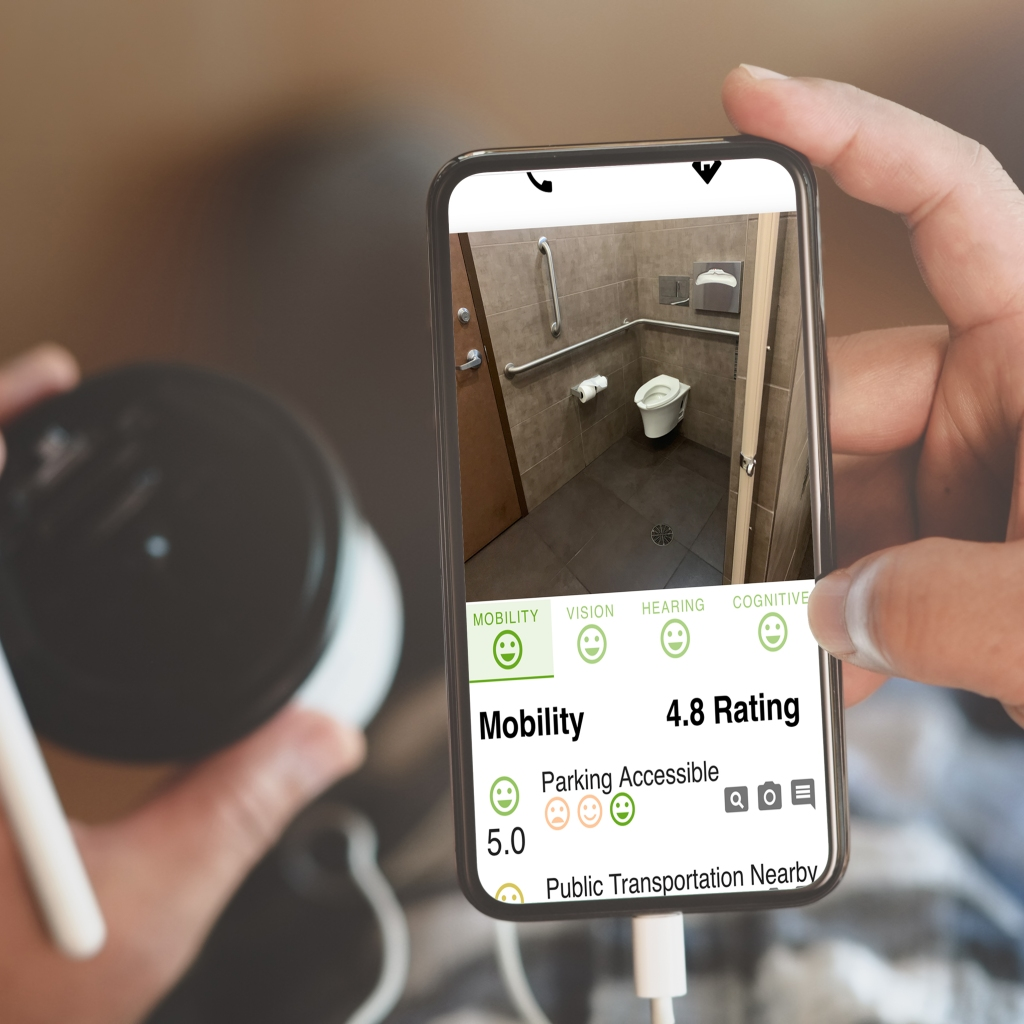 Lady holding a smartphone displaying Ability App mobility ratings and photos of accessible spaces at a local business. A photo of an accessible restroom is displayed on the phone.